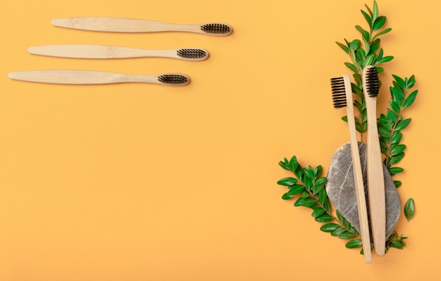 竹の歯ブラシは、黄色の背景にある天然石の上に5ピースのクローズアップ。黒い火山カーボン歯ブラシの嘘、コピースペースとフラットレイアウト。医学、環境に優しい、廃棄物ゼロのコンセプト
