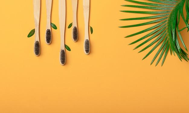 黄色の背景に緑の葉が付いた黒い毛の竹製の木製歯ブラシが5本あります。環境に優しいコンセプト、ゼロ廃棄物、リサイクル、エコ。コピースペースでフラットレイアウト