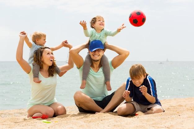 海のビーチでプレーする5人の陽性家族