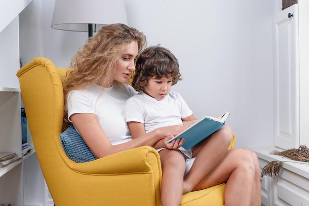 彼女の5歳の幸せな陽気な息子と柔らかい緑の椅子に座って、面白い本を読んで楽しんでいる魅力的な若い集中ママのクローズアップ