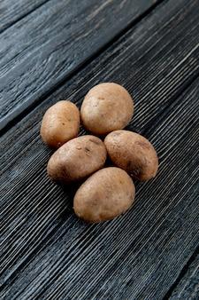 Вид сбоку картофеля на деревянном фоне с копией пространства 5