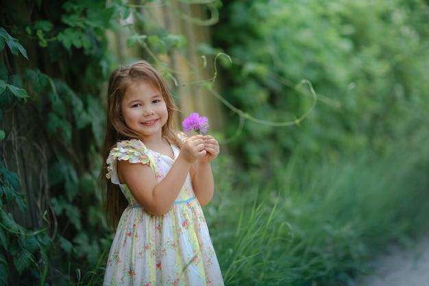 緑の植物で編んだフェンス近くの路上に立つ5歳の子供女の子