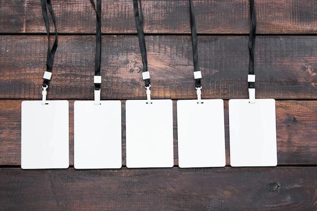 木製のテーブルにロープで5つのカードバッジ