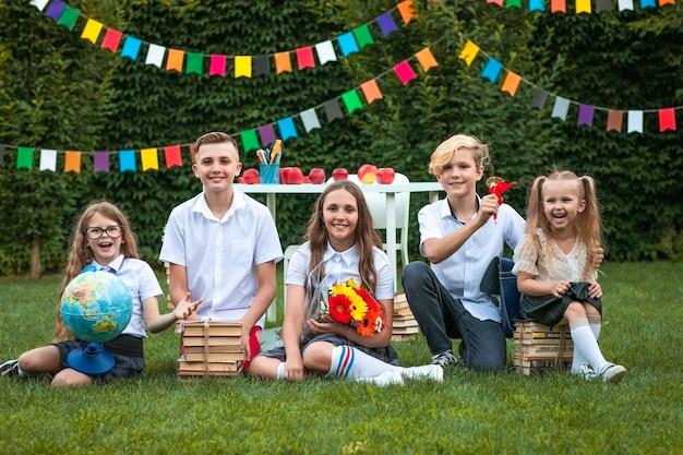 本、グローブ、フラグの背景に緑の芝生の上に座っている花を持つ5人のかわいい子供たち