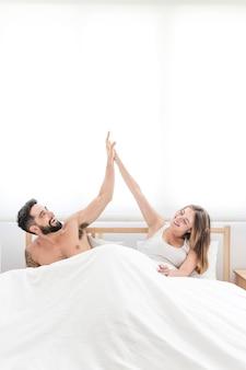 高い5を与えるベッドに座っている幸せなカップル