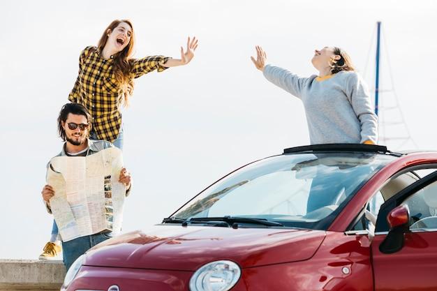 陽気な女性が車の近くの地図を見て男の近くに5を与える