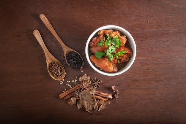 白いボウルと茶色の木製テーブルの上の5つのスパイスパウダーで豚肉のシチュー