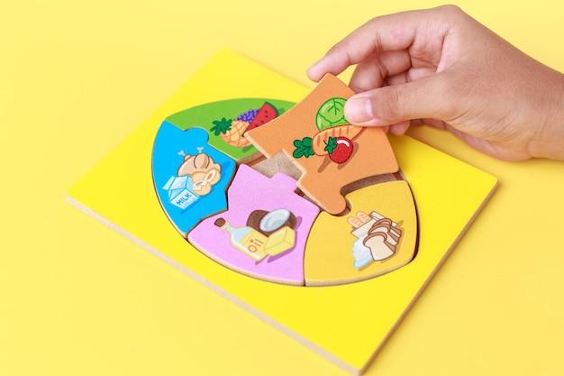 Закройте руки ребенка, держит деревянную головоломку из 5 групп продуктов. развитие ребенка