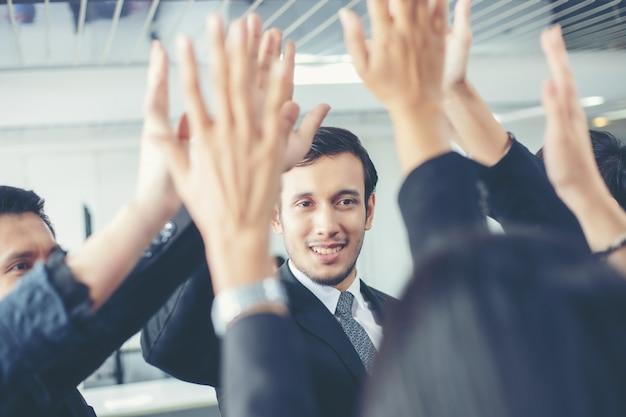 ハッピービジネスの人々がチームワークを示し、契約にサインした後に5人を与える