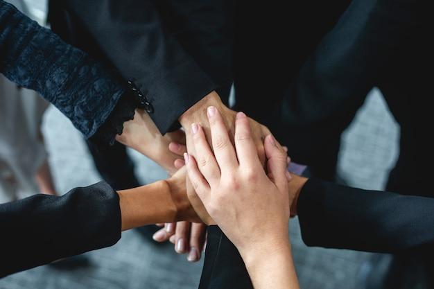 Счастливые бизнесмены показывая работу команды и давая 5 после подписания соглашения или контракта с иностранными партнерами в интерьере офиса.