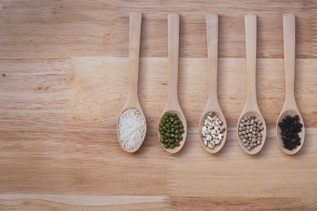 木のテーブルに5スプーンの場所に置かれた穀物
