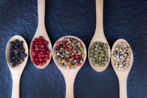 木のスプーンでコショウの5種類のフラットレイアウト、黒の背景、健康食品の概念上の位置のための場所