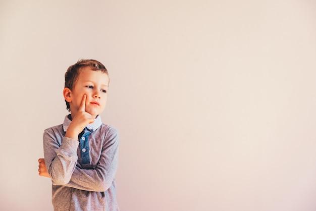 コピースペース領域と白い背景の上の非常に表現力豊かな思いやりのあるジェスチャーで5歳の男の子。