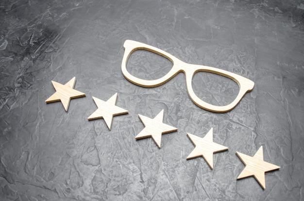 木製のメガネとコンクリートの背景に5つ星です。高品質のメガネ。