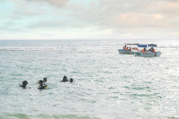 5人のスキューバダイバーがインド洋の水面を泳ぎます。