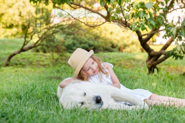 公園で大きな白い犬を持つ少女。白いドレスを着た美しい5歳の女の子が夏の散歩中に彼女のお気に入りの犬を抱擁します。