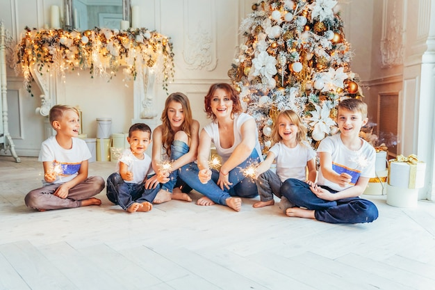 幸せな家族母と家でクリスマスイブにクリスマスツリーの近くで線香花火を遊んでいる5人の子供。お母さん、娘、冬の装飾と明るい部屋で息子。クリスマス新年のお祝いの時間
