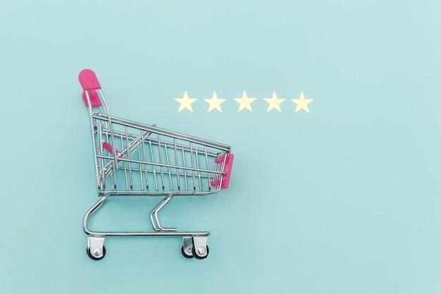 Малая тележка нажима бакалеи супермаркета для ходя по магазинам игрушки при колеса и оценка 5 звезд изолированная на пастельной голубой предпосылке. розничный потребитель, покупающий онлайн оценку и обзор концепции.