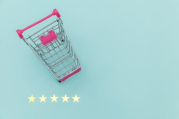 車輪とパステルブルーの背景に分離された5つ星評価ショッピンググッズの小さなスーパーマーケットの食料品のプッシュカート。オンライン評価とレビューのコンセプトを買う小売消費者。