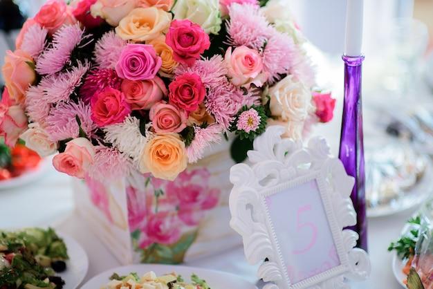 夕食のテーブルにピンクの花束の前に白いフレームのスタンドを入れて5番