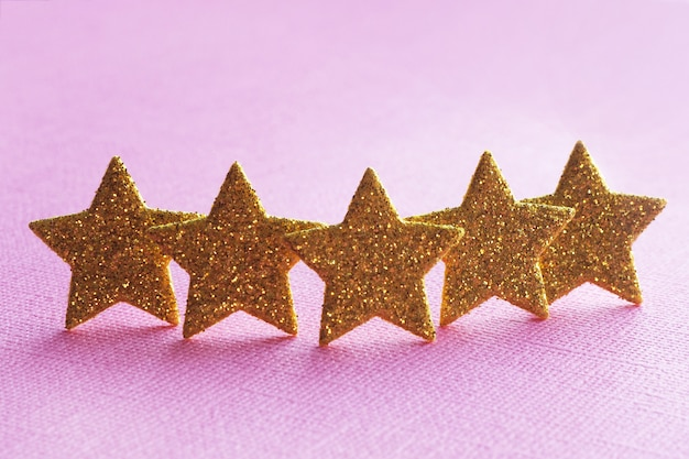 ピンクの背景に5つの金色の星。