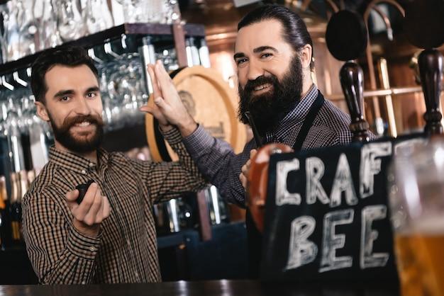 ひげを生やした男性ウェイターはクラフトビールパブで5を与えます。