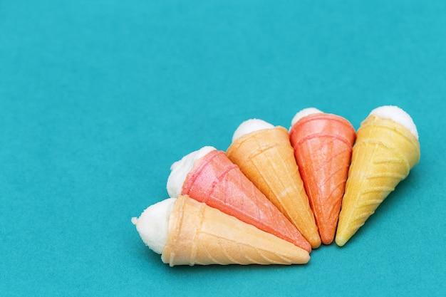 5 конусов мороженого на бумажной предпосылке с пустым космосом для текста. выборочный фокус. праздничный фон.