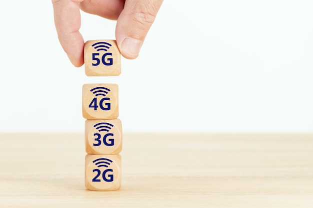 5g network evolution concept. hand holding a wooden block with text and symbol.