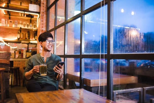 Красивый молодой человек азиаты работают на ноутбуках, смотрят видео на смартфонах, держат мобильные телефоны и путешествуют по сети, используя высокоскоростной 5g.