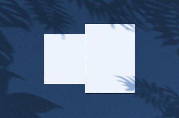 パームシャドウオーバーレイを備えた5x7インチの空白のホワイトペーパーシート。モダンでスタイリッシュなグリーティングカードや結婚式招待状のモックアップ。 2020年の古典的な青の色