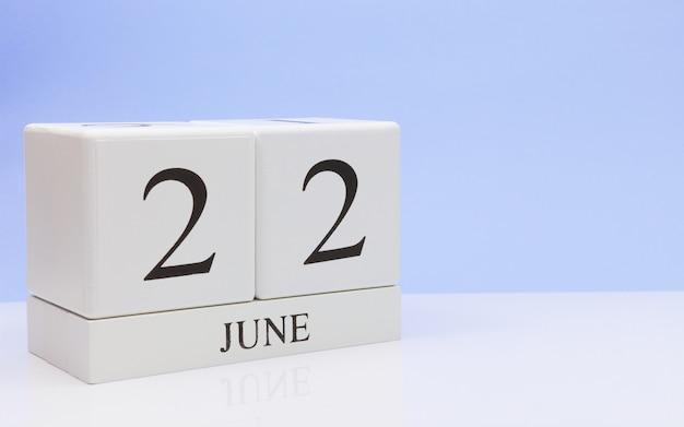 6月22日月22日、白いテーブルに毎日のカレンダー
