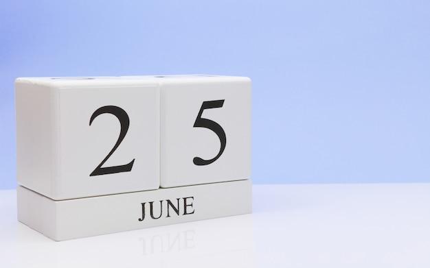 6月25日月25日、白いテーブルに毎日のカレンダー