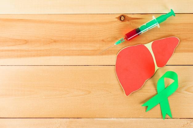 世界肝炎の日。 6月28日。緑色のヒスイテープ、肝臓、シリンジ、木製のテーブルに血液を入れる。