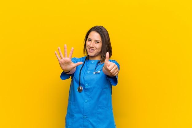 笑顔で友好的で、6番または6番を手で前方に向けて、黄色の壁に対して隔離されたカウントダウン
