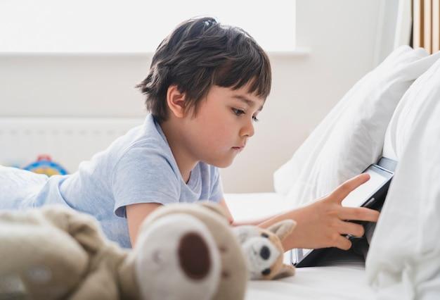 ふわふわのおもちゃで横になってタブレットで漫画を見ている6〜7歳の男の子、朝のゲームでベッドに横になっている幸せな子供、ベッドルームで一人で楽しんでリラックスしている子供、