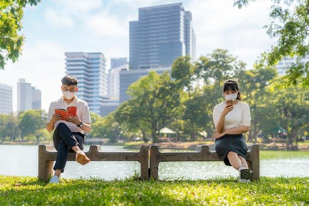 アジアの若い男性と女性が本を読んでスマートフォンでチャットし、6フィートの距離にあるマスクの着席距離を着て、感染リスクの社会的距離を隔てるcovid-19ウイルスから保護する