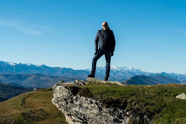 美しい自然の風景とスペイン北部の山歩きの後にポーズをとる60歳の男性