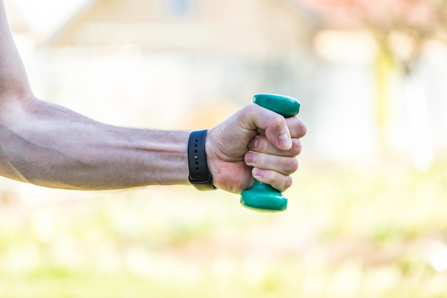 男の手がプラスチック製のスポーツダンベルを持っています。 60年後のスポーツ活動。健康的なライフスタイルのコンセプトです。