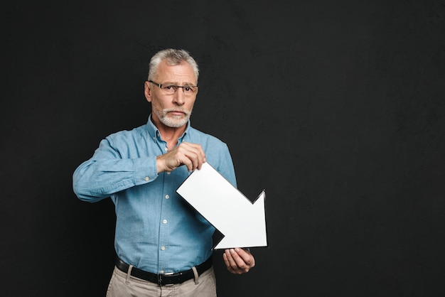 黒の壁に分離された下向きの空白の音声矢印ポインターを保持している眼鏡をかけている灰色の髪の欲求不満のひげを生やした紳士60年代の画像