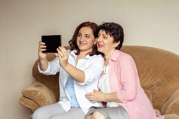 若い女性と彼女の60歳の母親は、ビデオコミュニケーションを使用してタブレットでコミュニケーションをとっています。