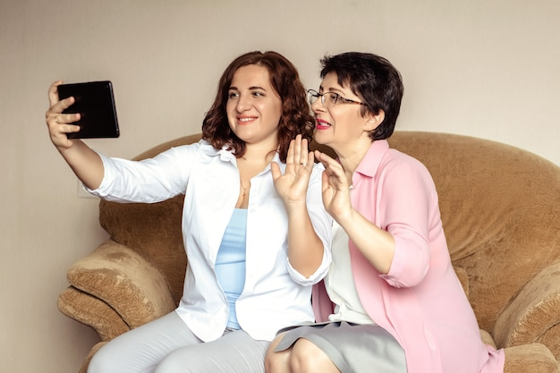 Молодая женщина и ее мать, 60 лет, общаются на планшете с помощью видеосвязи.
