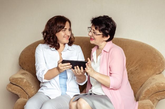 Молодая женщина учит 60-летнюю маму общаться с помощью видеосвязи на планшете.