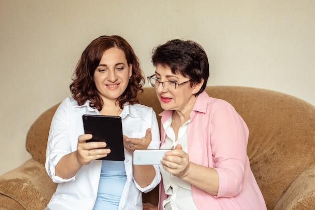 若い女性が60歳の母親にタブレットでビデオ通話を使ってコミュニケーションするように教えています。