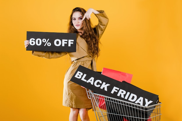 Стильная молодая женщина имеет черную пятницу с 60 скидками войти в тележку с красочными сумками и сигнальной лентой, изолированных на желтом