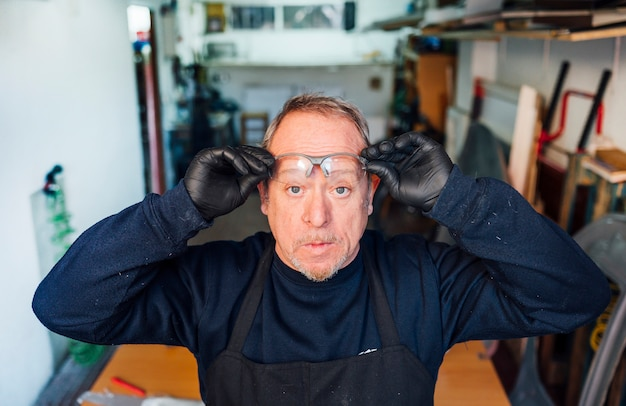 62 year old man putting on safety glasses in the fiber workshop.