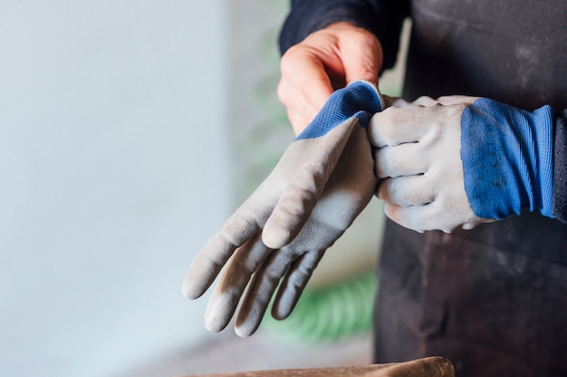 62 year old man working in the fiber shop, puts on gloves