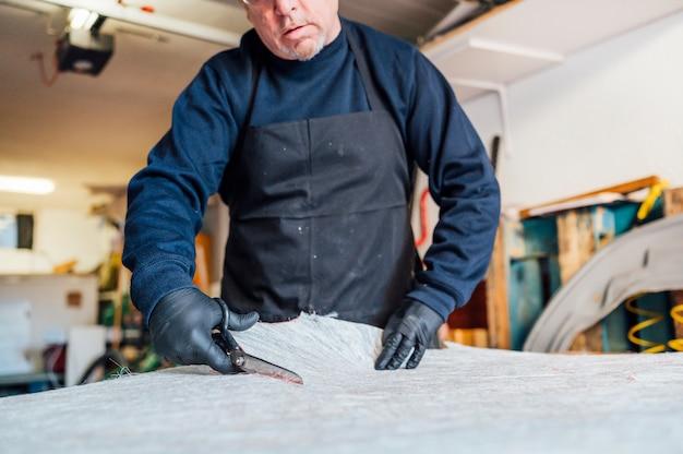 62-летний мужчина резки ножницы в мастерской.