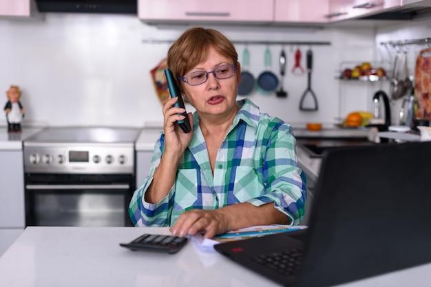 65-летняя женщина работает дома с ноутбуком и разговаривает по телефону.