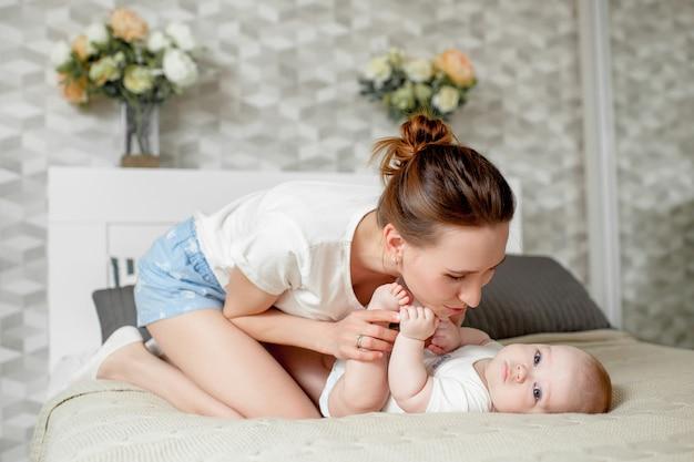 ママは自宅のベッドで6ヶ月の赤ちゃんと遊ぶ