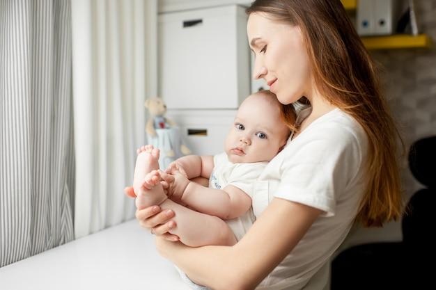 Мама играет с ребенком 6 месяцев на кровати дома